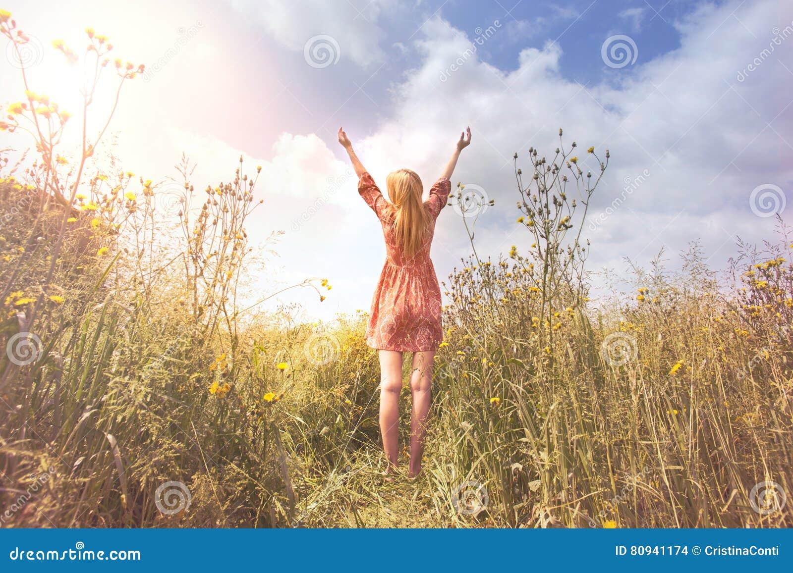Het jonge die vrouw ontspannen met wapens aan de hemel in het midden van de aard worden opgeheven