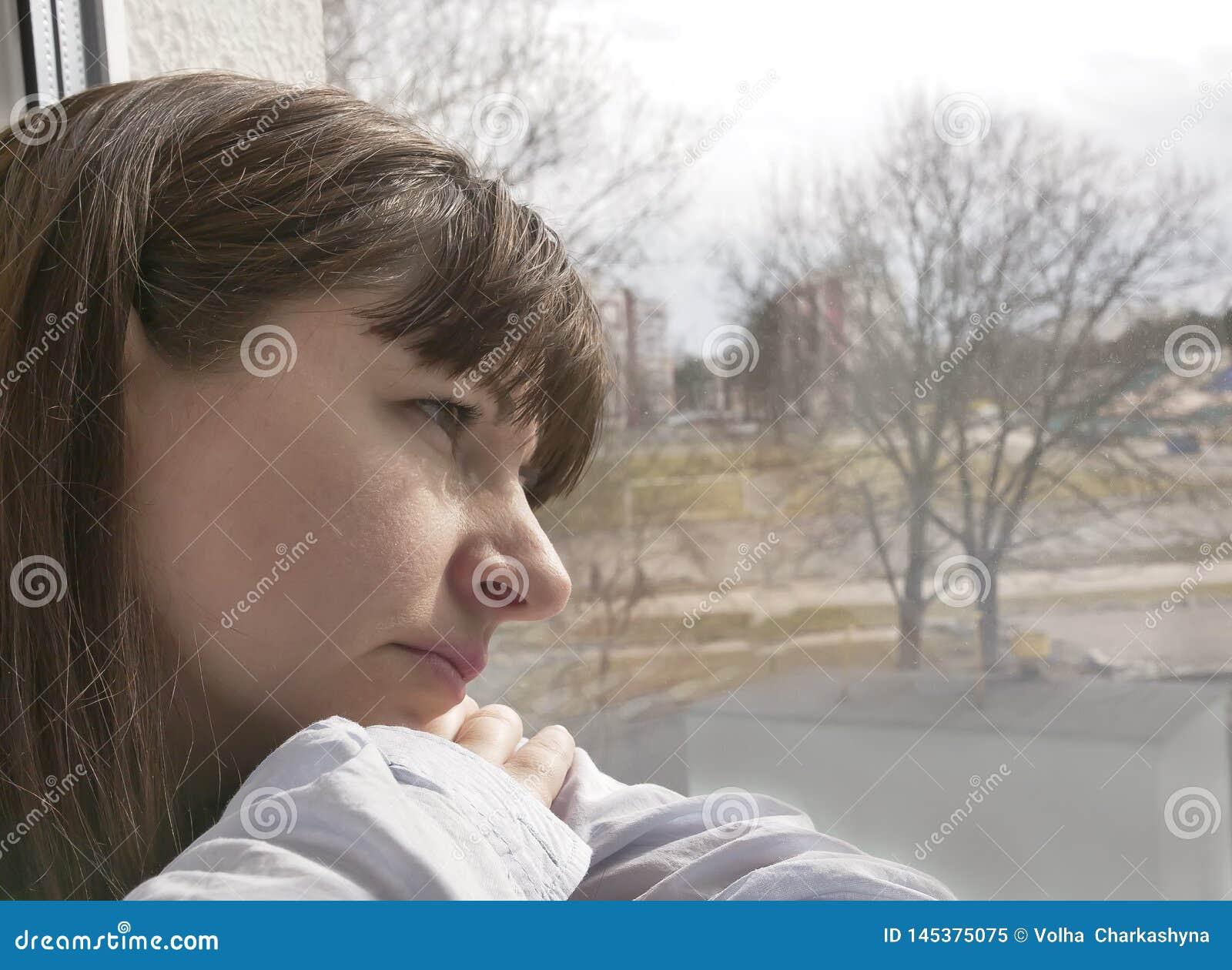 Het jonge donkerbruine vrouw droevige kijken venster, close-up