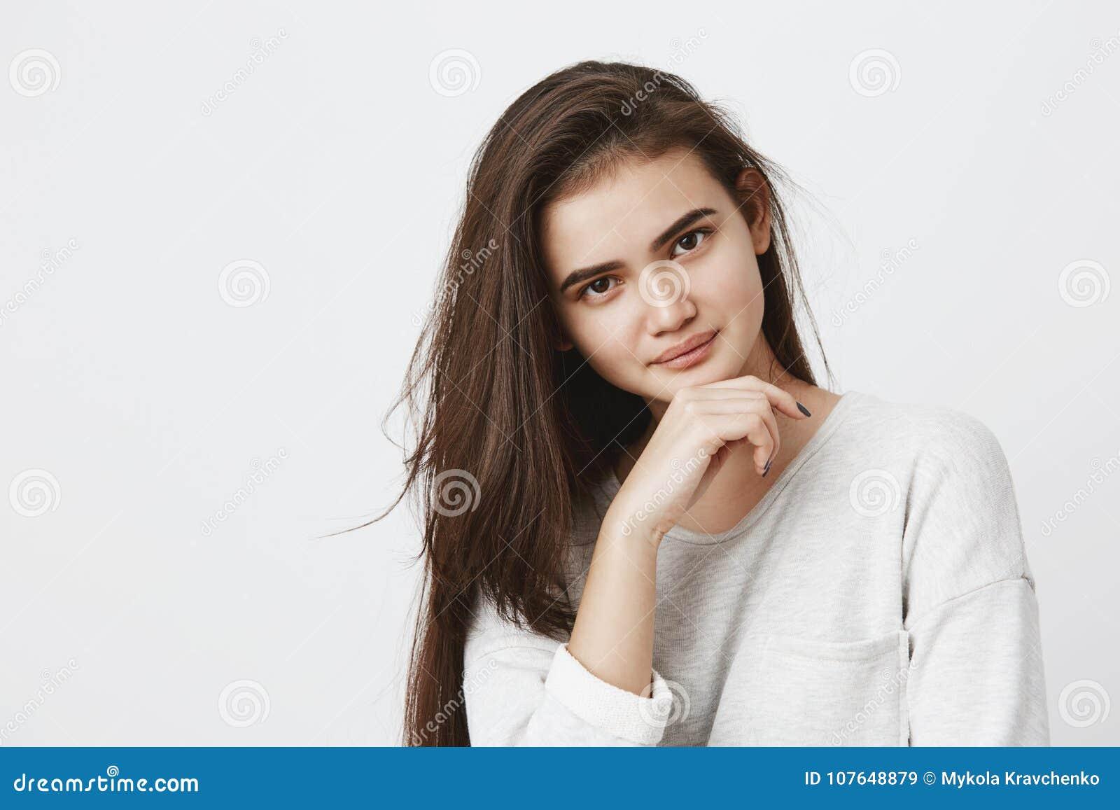 Het jonge donkerbruine wijfje met ovaal gezicht, donkere aantrekkelijke ogen die haar hebben kleedde zich los in de lang-sleeved