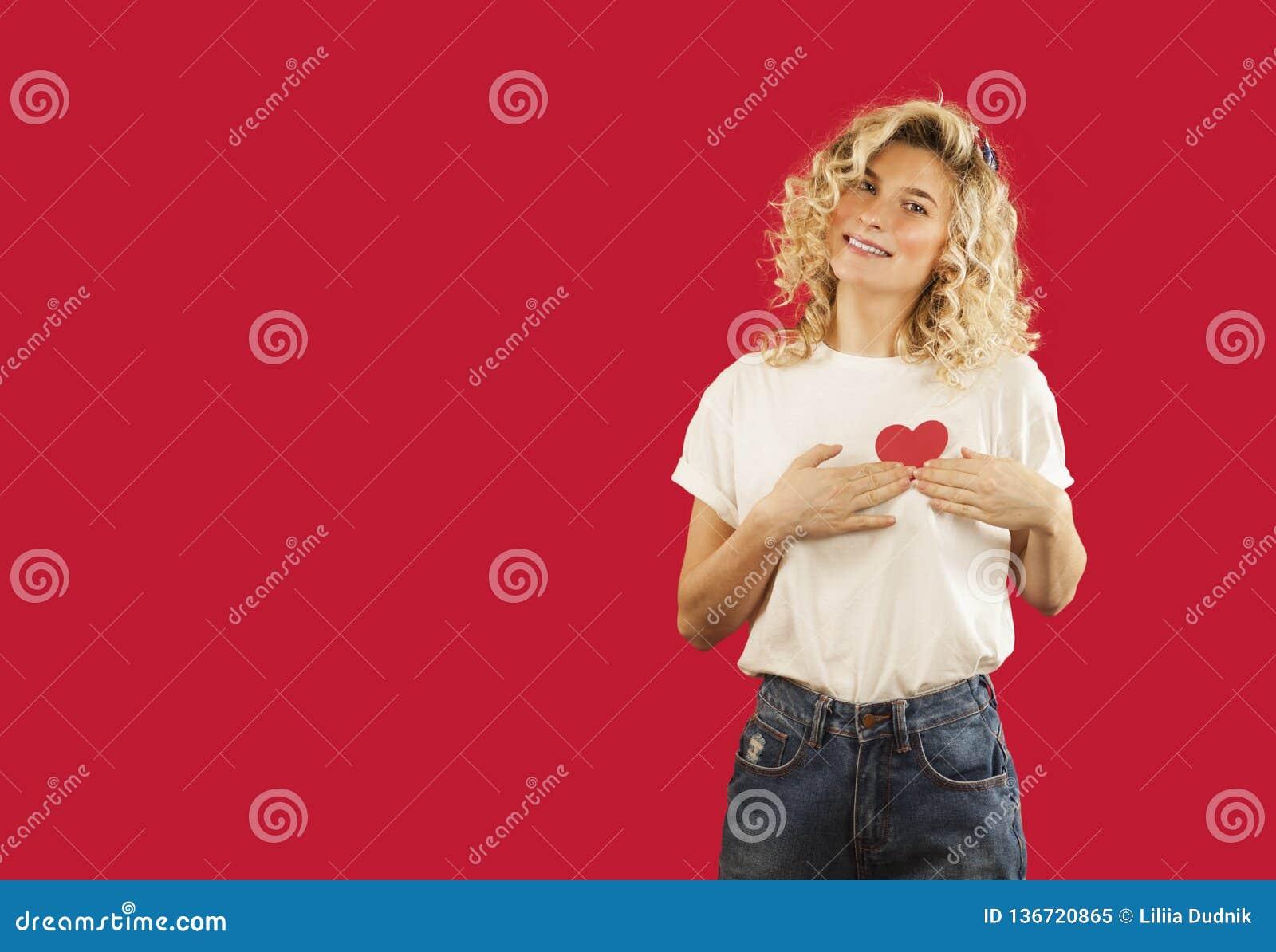 Het jonge emotionele meisje met een rood hart in haar handen bevindt zich op een geïsoleerde rode achtergrond Het concept van de