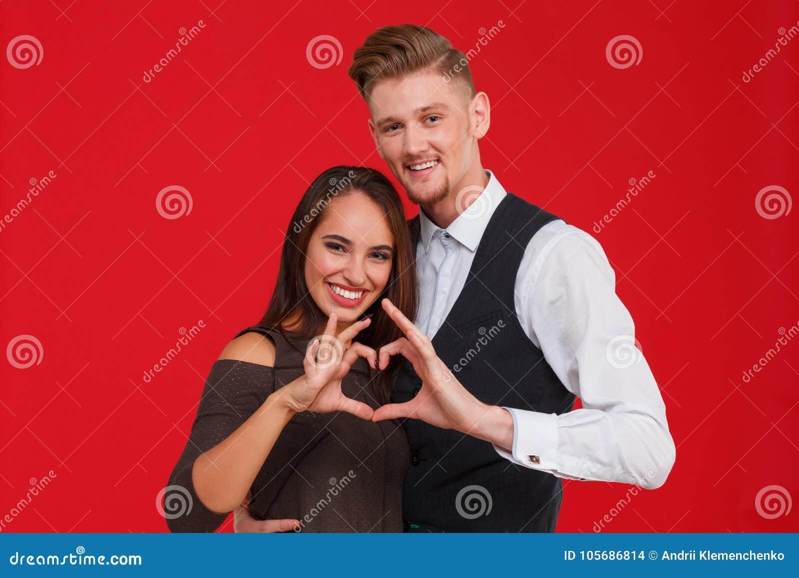 Het jonge en mooie paar in liefde maakt een hart op een rode achtergrond Het concept de Dag van Valentine ` s
