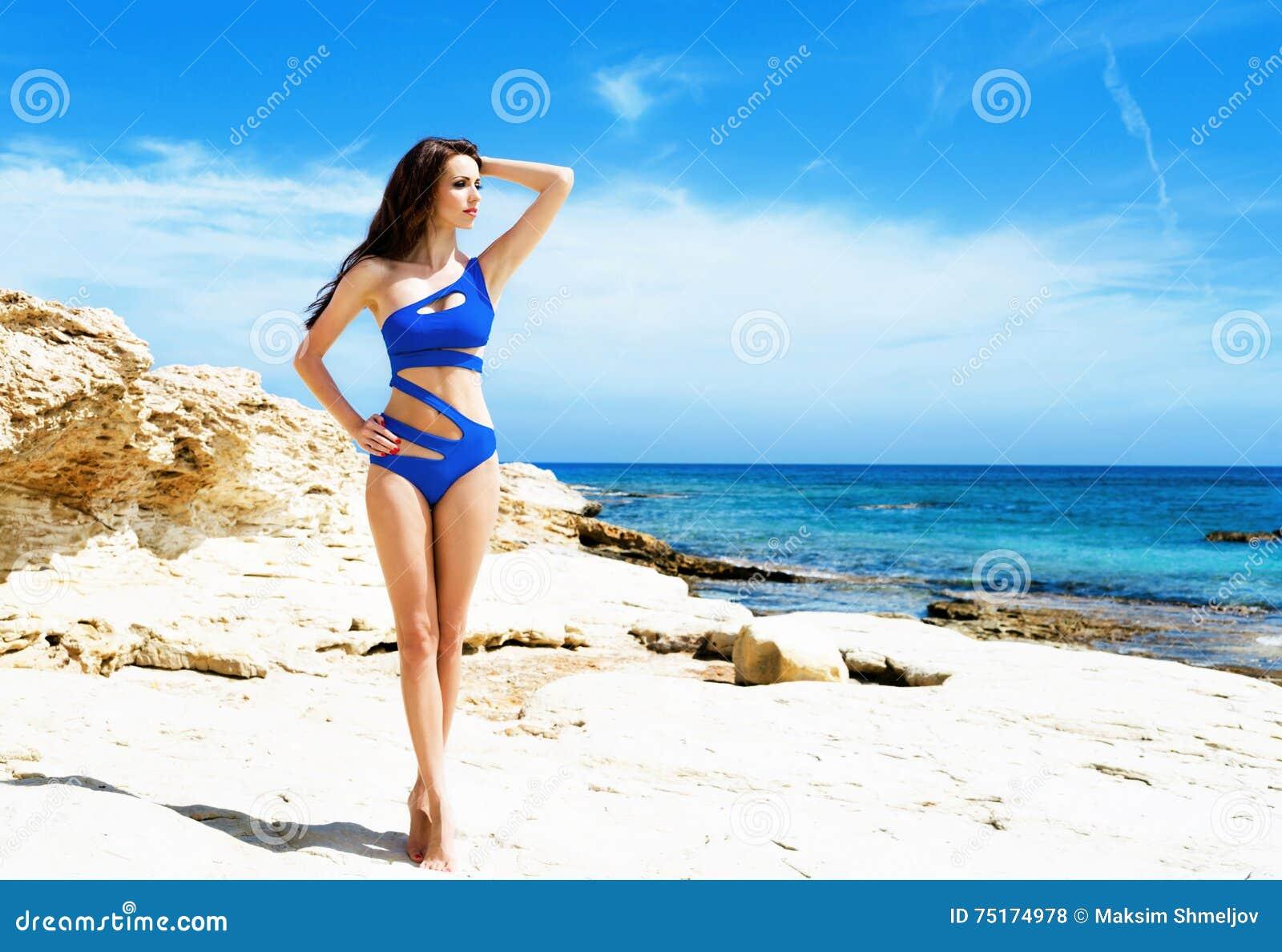 Het jonge en sexy vrouw stellen in een blauw zwempak op het strand