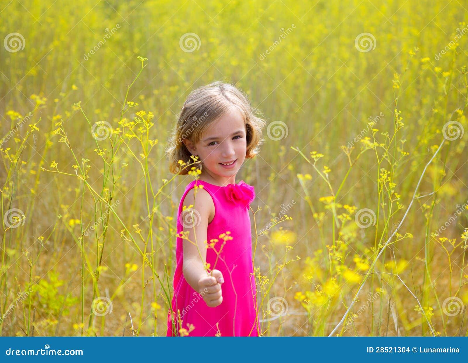 Het jonge geitjemeisje van het kind in gebied van de lente het gele bloemen en roze kleding