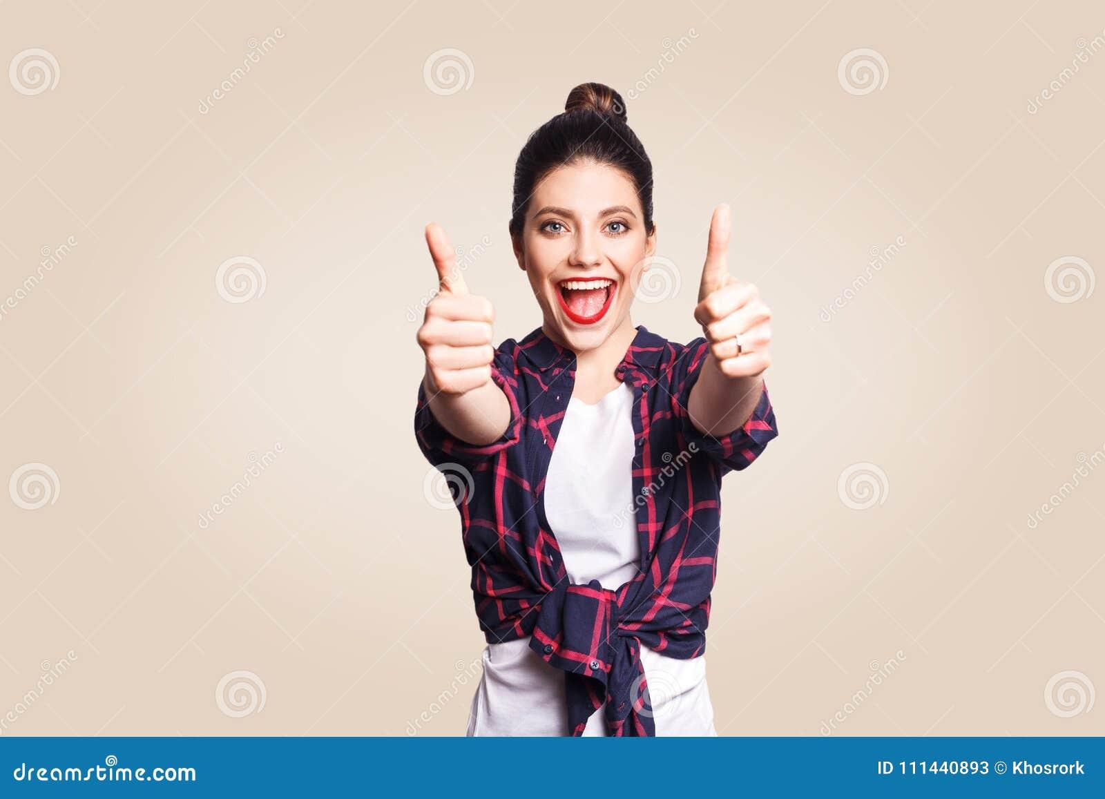 Het jonge gelukkige meisje met toevallig stijl en broodjeshaar beduimelt omhoog haar vinger, op beige blinde muur met exemplaar h