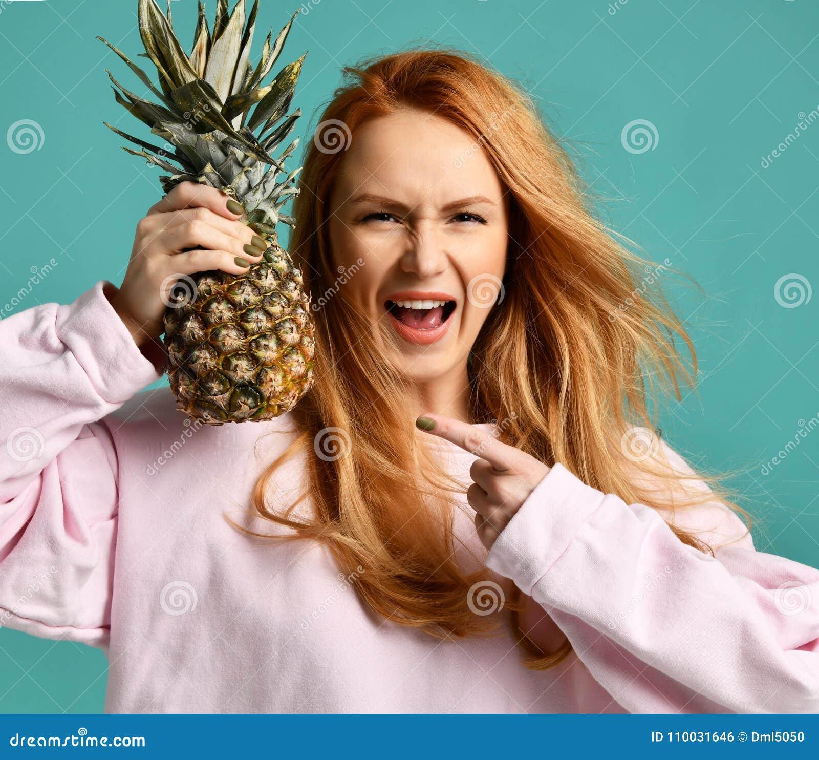 Het jonge gelukkige mooie sexy vrouw stellen die met ananasfruit lachen