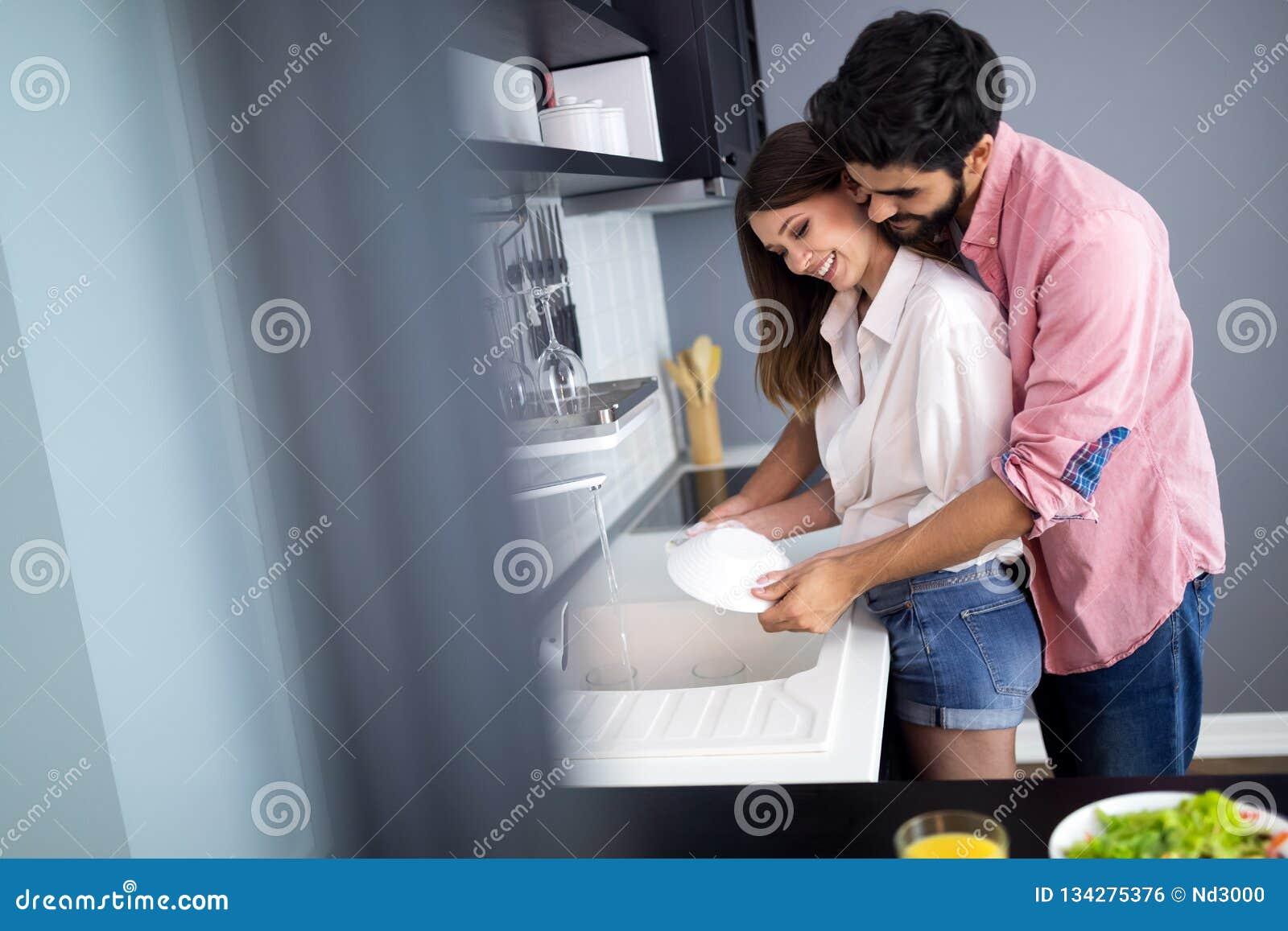 Het jonge gelukkige paar wast schotels terwijl het doen van thuis het schoonmaken