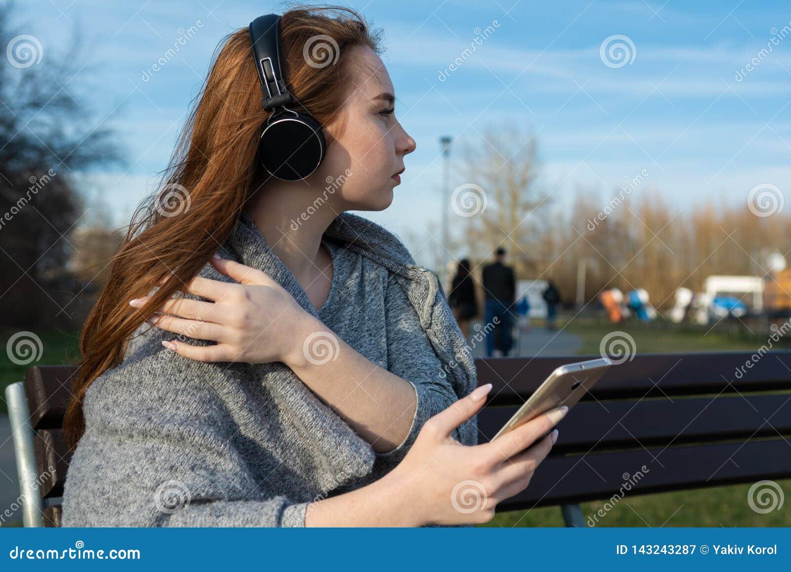 Het jonge, gelukkige roodharigemeisje in de lente in het park dichtbij de rivier luistert aan muziek door draadloze bluetoothhoof