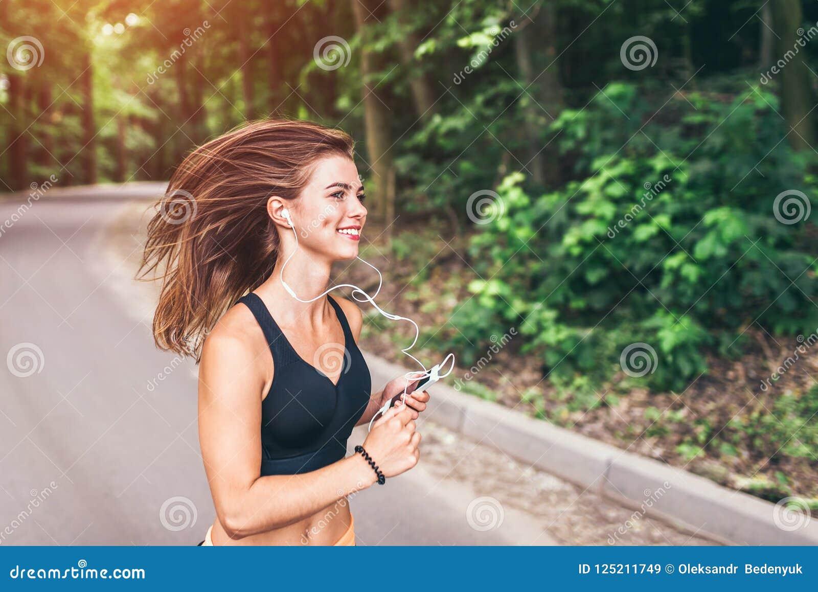 Het jonge geschiktheidsmeisje lopen en het luisteren muziek in het park