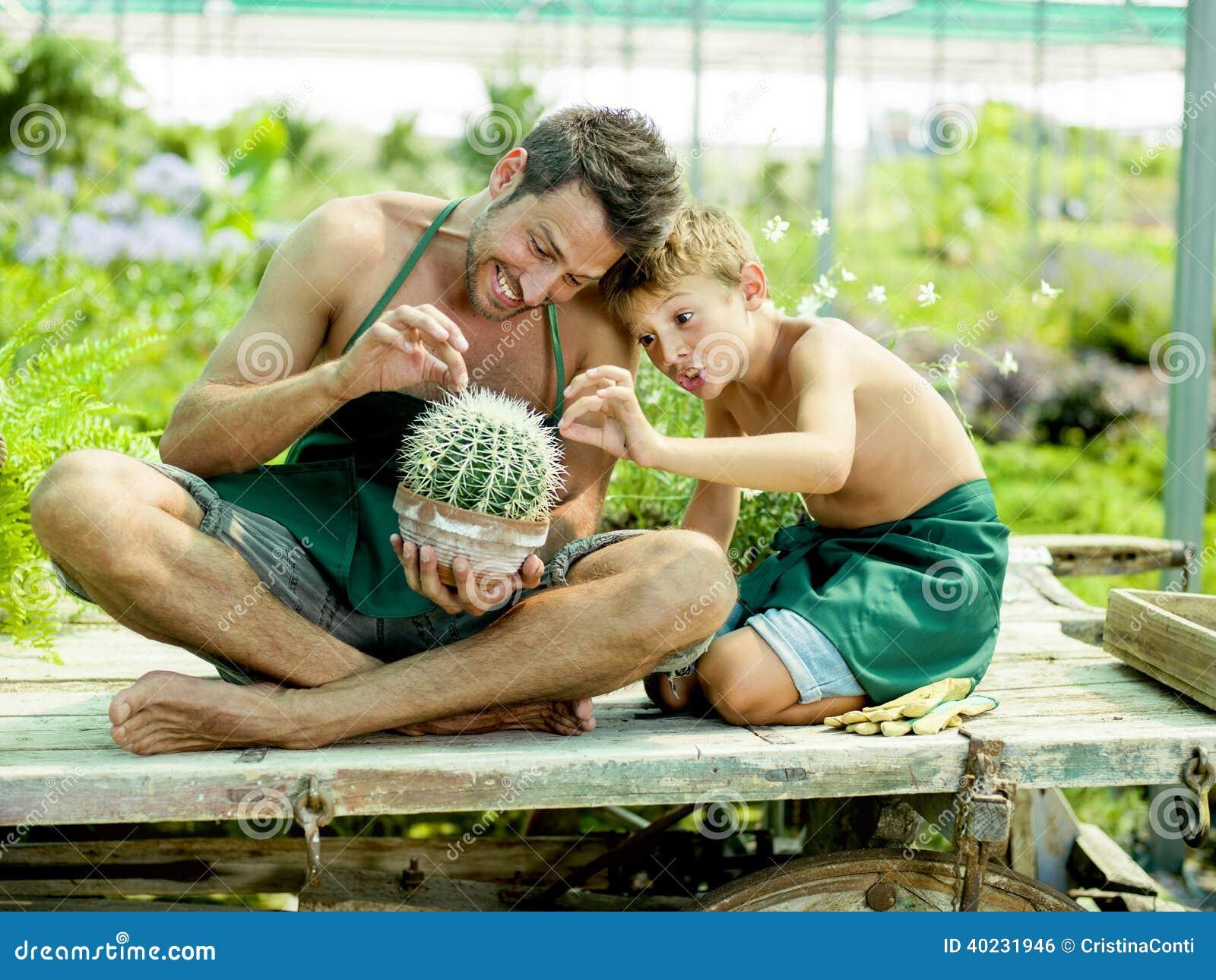 Het jonge jongen spelen met zijn vader in een serre