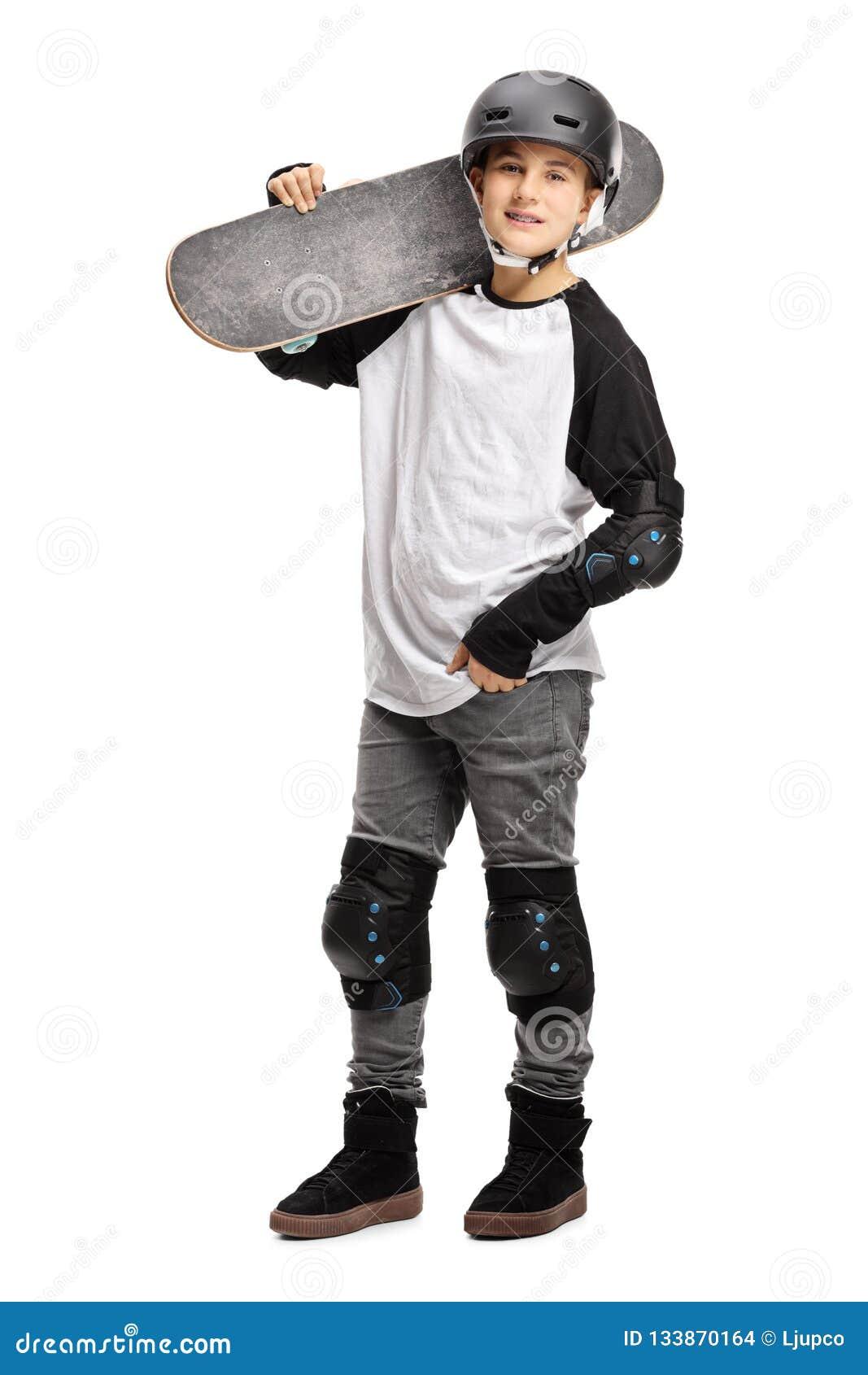 Het jonge jongen stellen met een skateboard op zijn schouder en een helm