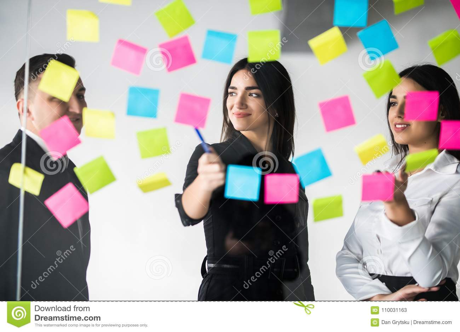 Het jonge mannelijke en vrouwelijke medewerkers schrijven die nota s voor collega s die het productieve werk proces in bureau pla