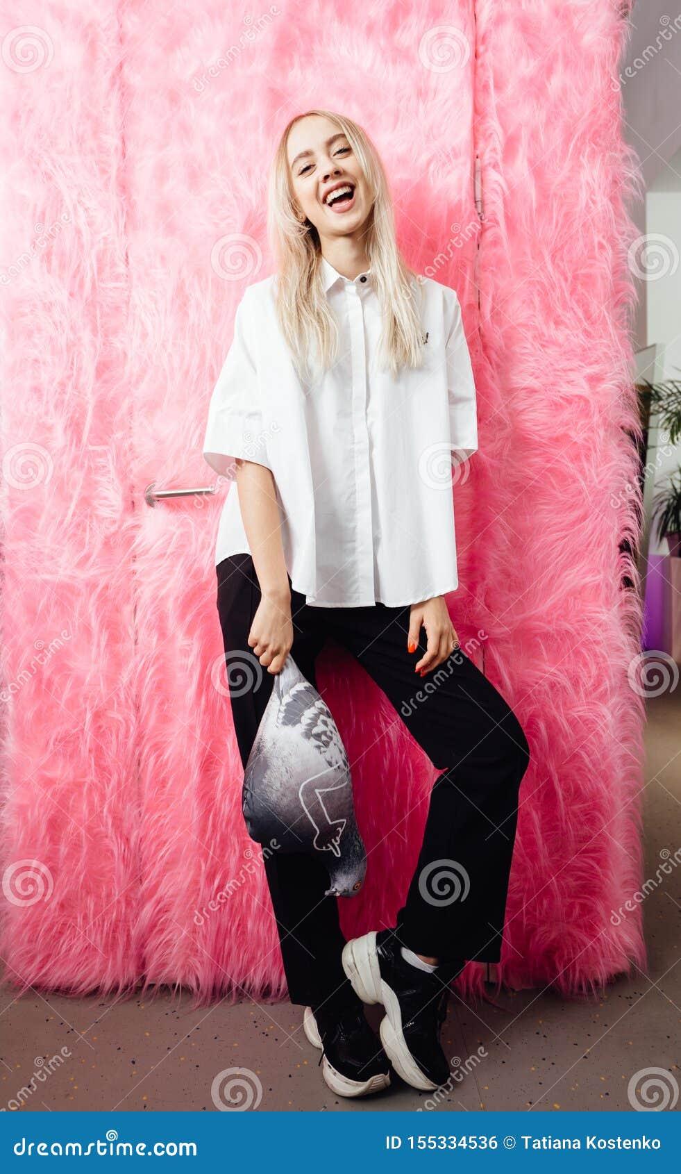 Het jonge meisje blogger gekleed in modieus wit overhemd en zwarte broeken stelt met met een zacht stuk speelgoed in de vorm van