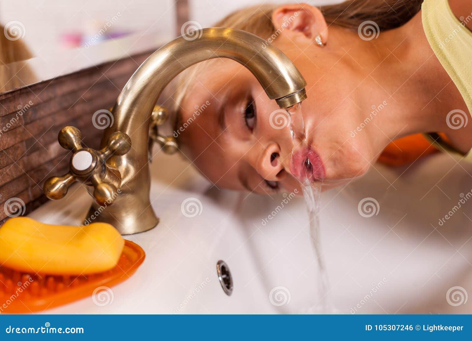 Het jonge meisje drinken van de badkamerstapkraan