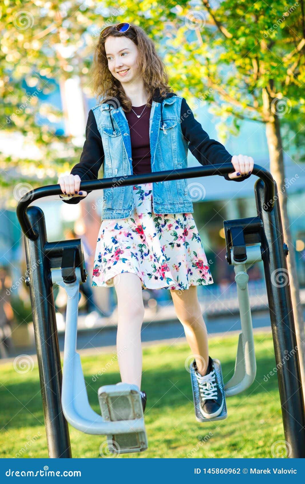 Het jonge meisje kleedde zich in rokoefening die een gymnastiekmachine in werking stelt openlucht
