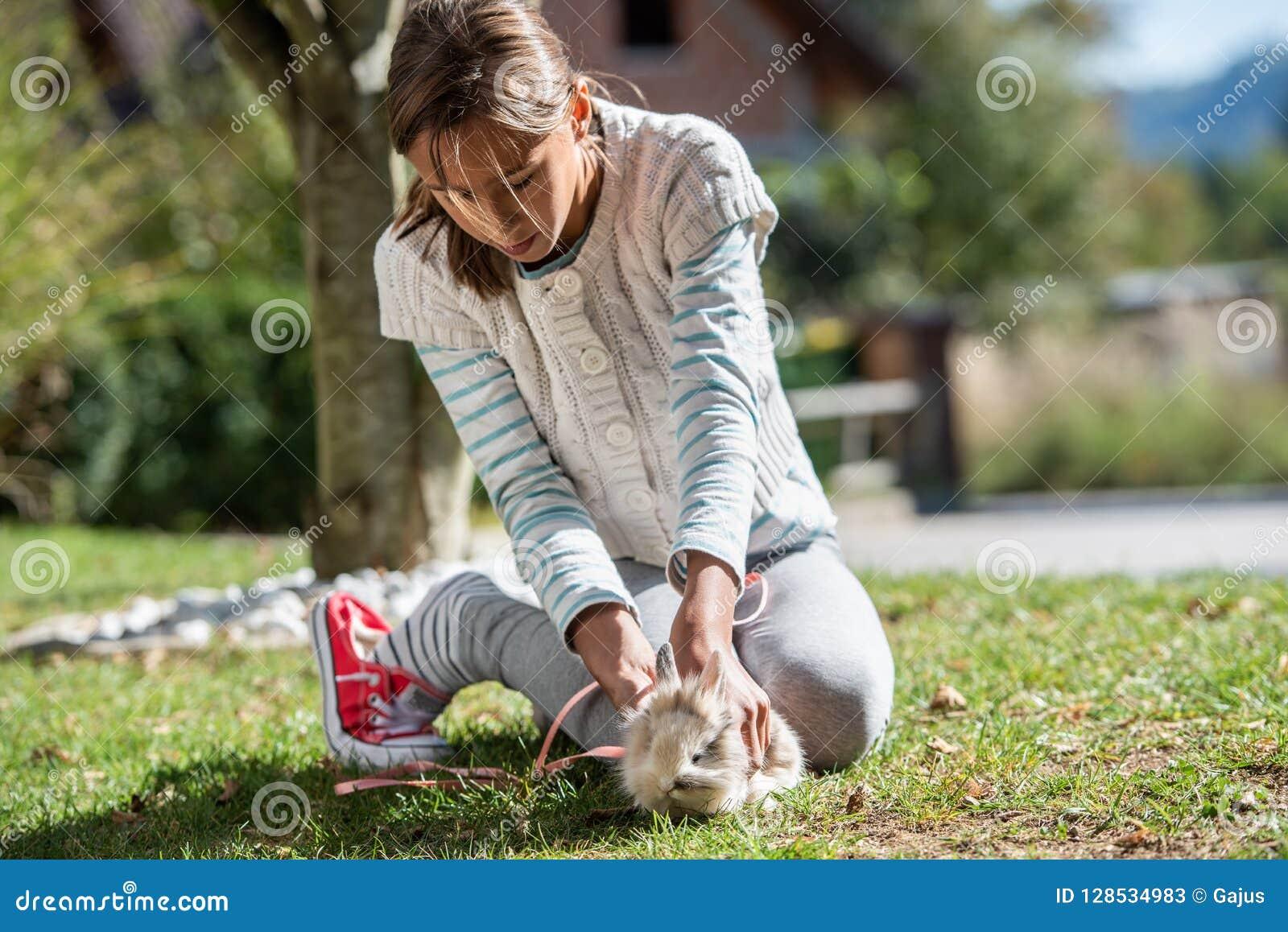 Het jonge meisje spelen met haar huisdierenkonijn