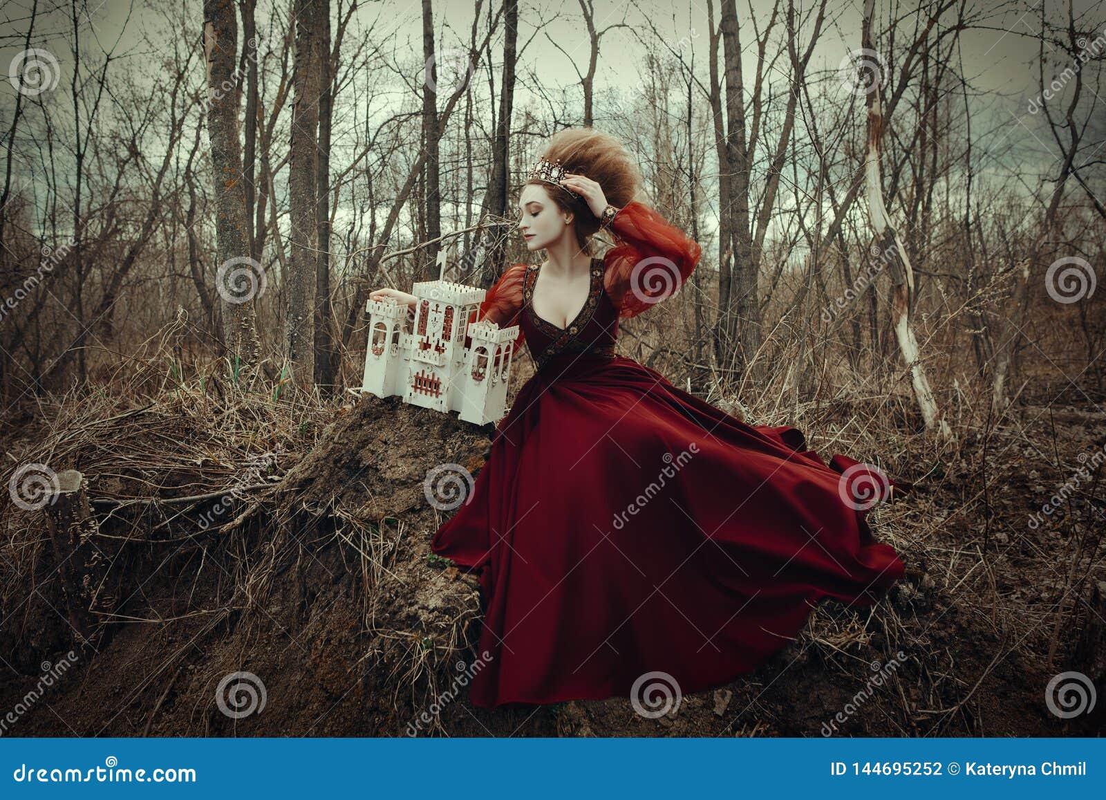 Het jonge meisje stelt in een rode kleding met creatief kapsel