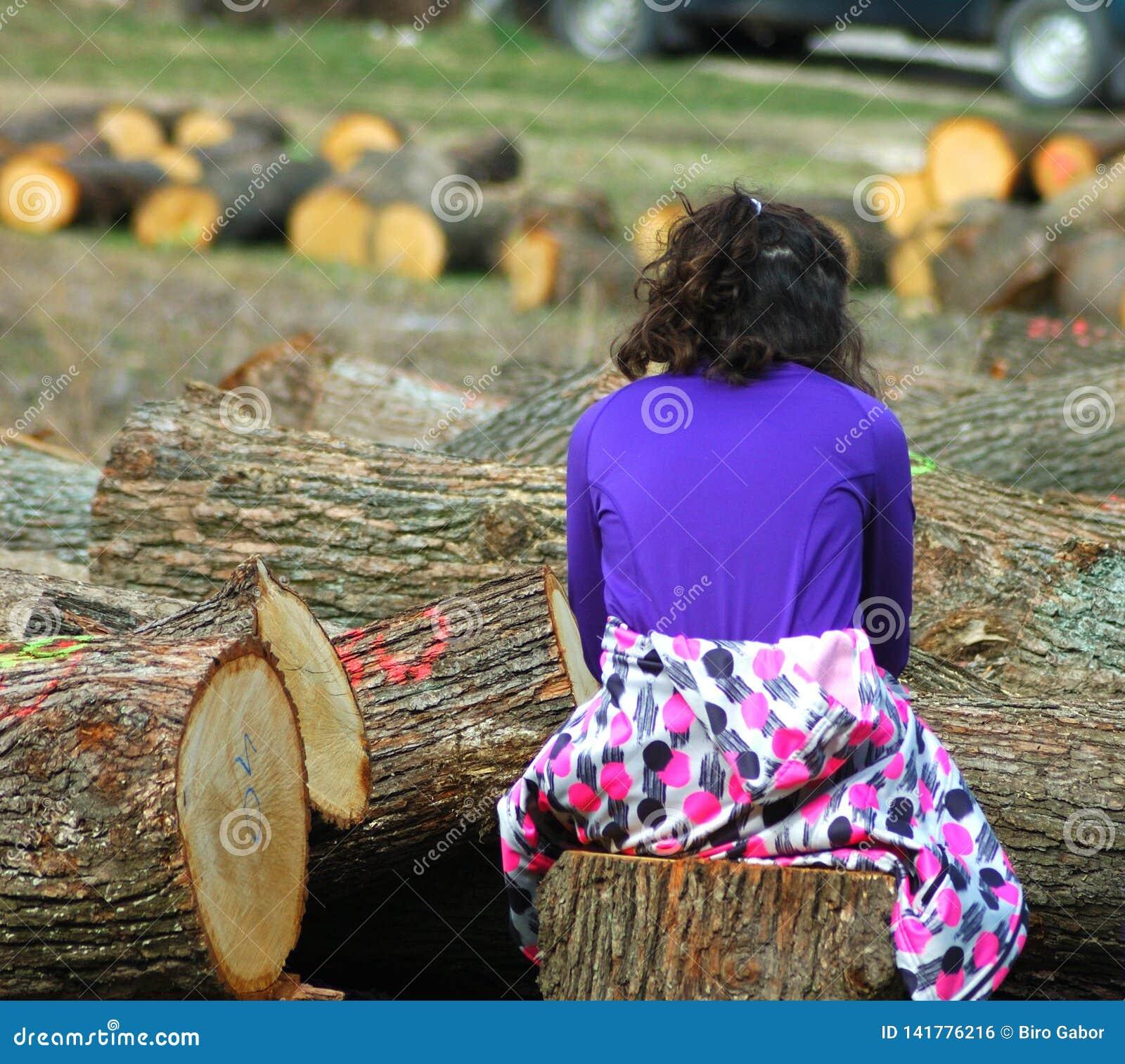 Het jonge meisje tussen cutted boom