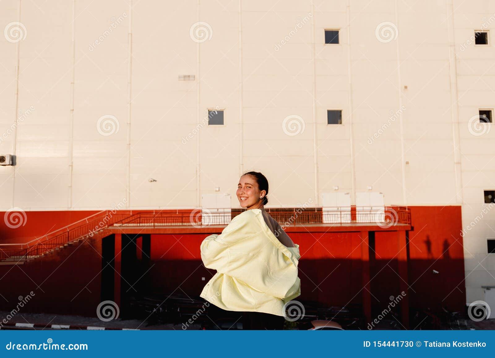 Het jonge modieuze meisje stelt in de straat voor het stedelijke gebouw in de warme dag