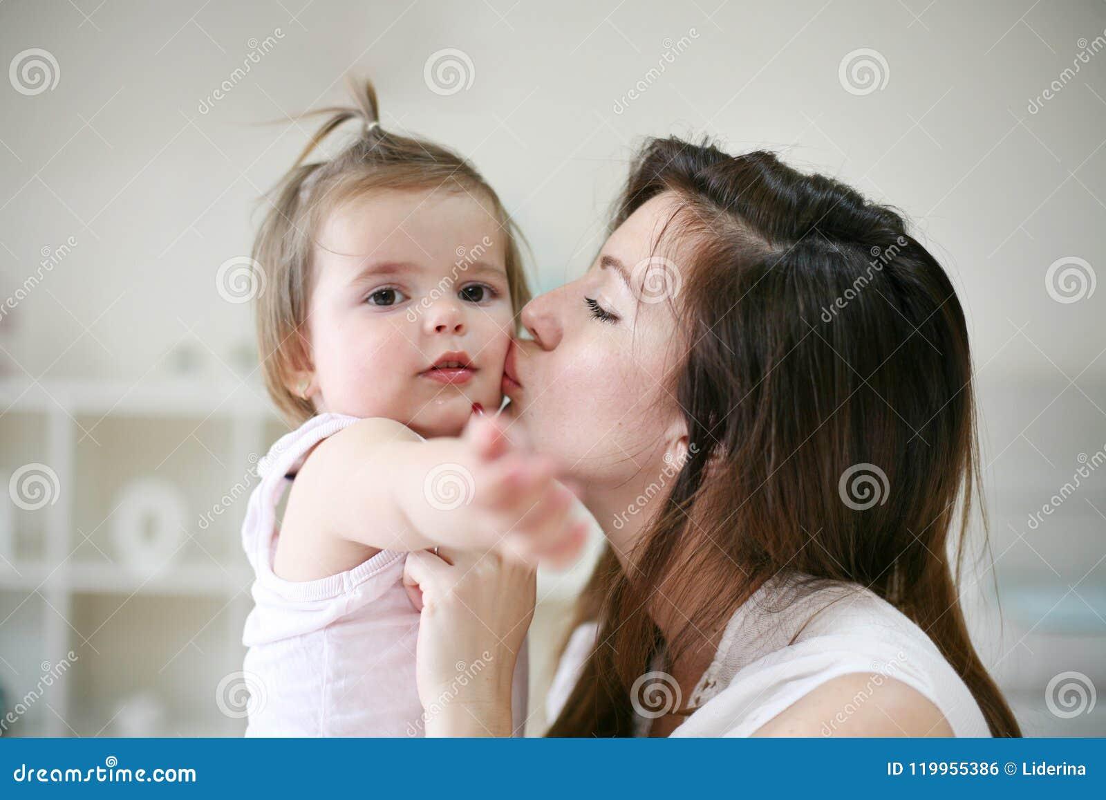 Het jonge moeder spelen met haar babymeisje in bed Moeder het kussen