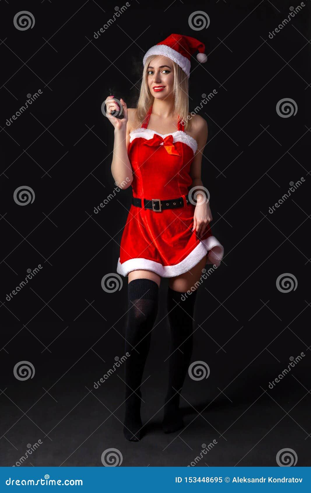 Het jonge mooie blondemeisje in een sexy rood kostuum van het Sneeuwmeisje of Santa Claus met vape in hand op een zwarte isoleerd