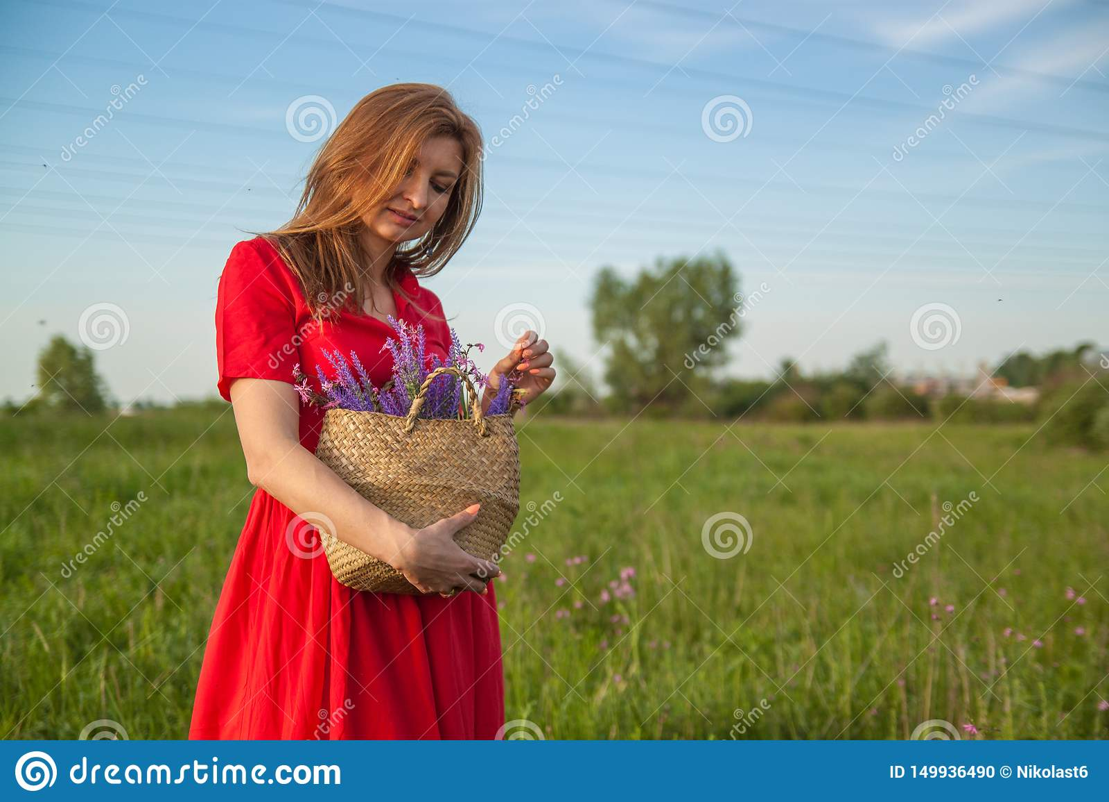 Het jonge mooie blondevrouw smilling met bloemen in aard in de zomer
