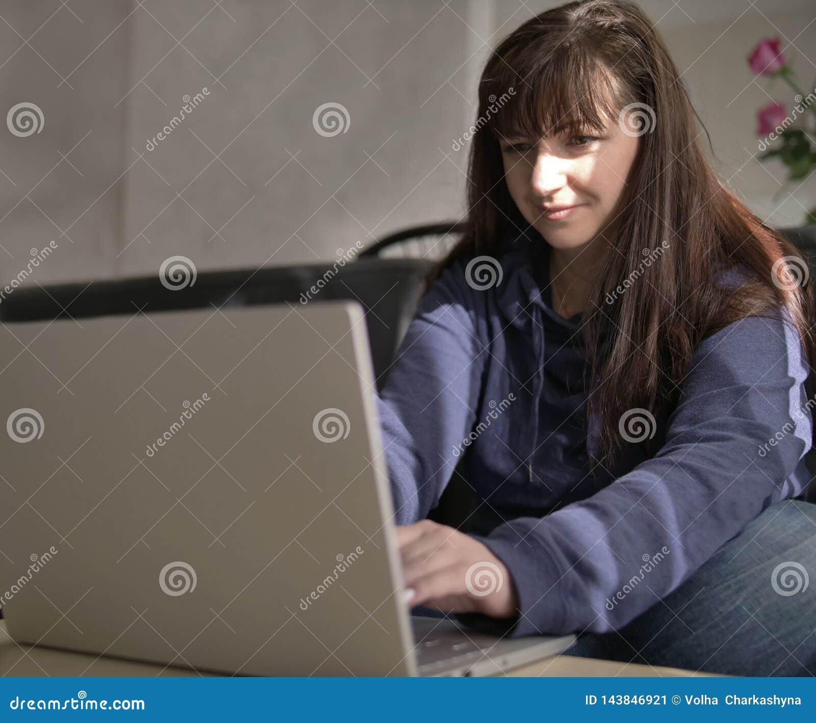 Het jonge mooie brunette glimlacht terwijl het typen op laptop