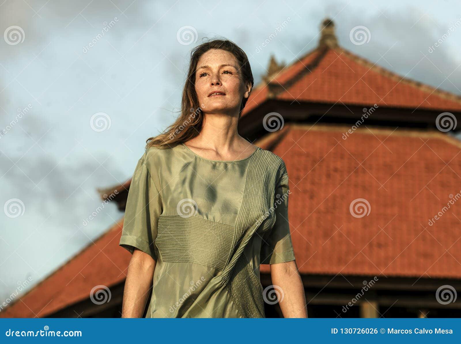 Het jonge mooie en aantrekkelijke blonde die vrouw stellen als schoonheidsmannequin voor Aziatische tempel wordt geïsoleerd die e