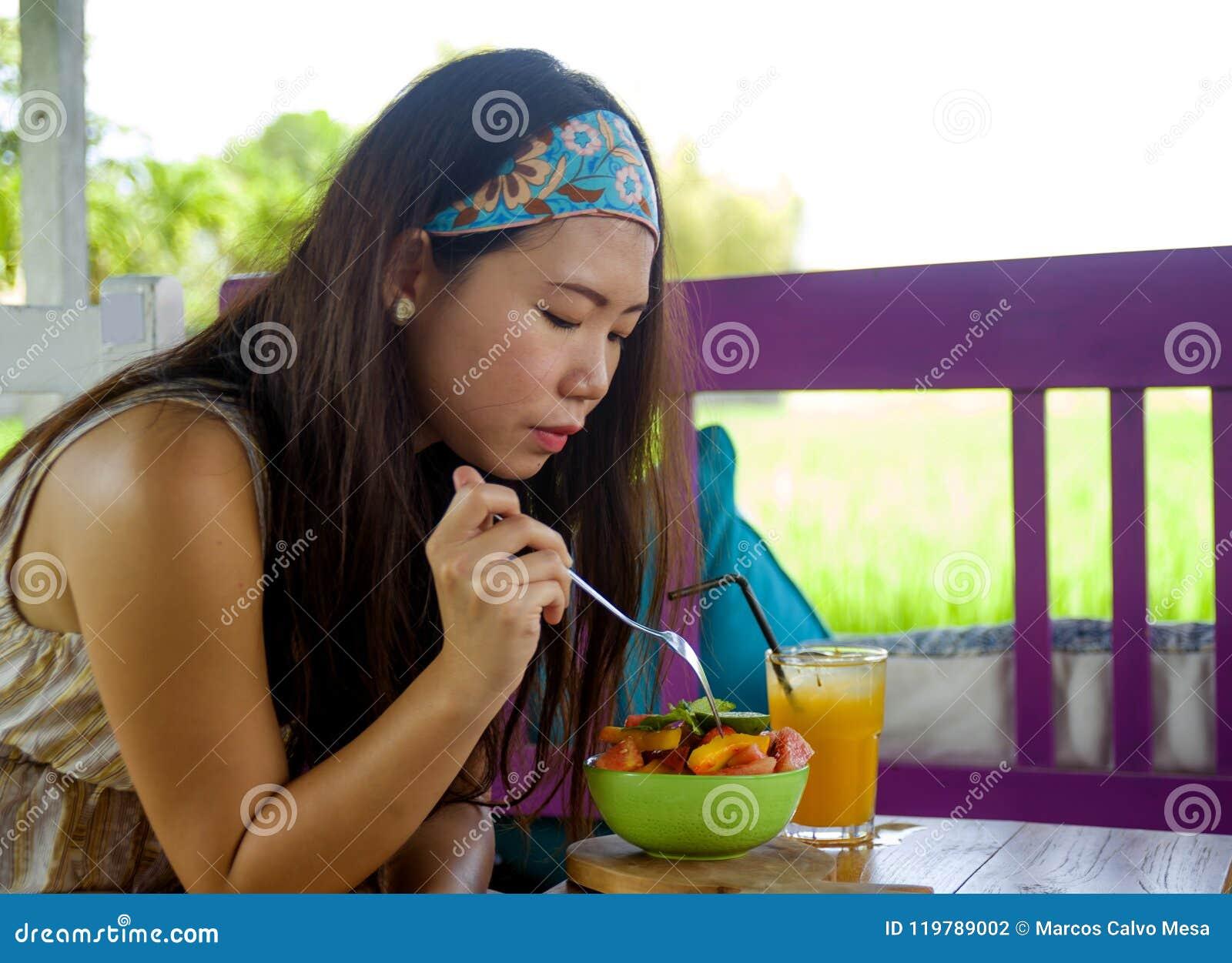 Het jonge mooie en gelukkige Aziatische Koreaanse vrouw het drinken jus d orange die gezonde salade eten bij de winkel van de nat