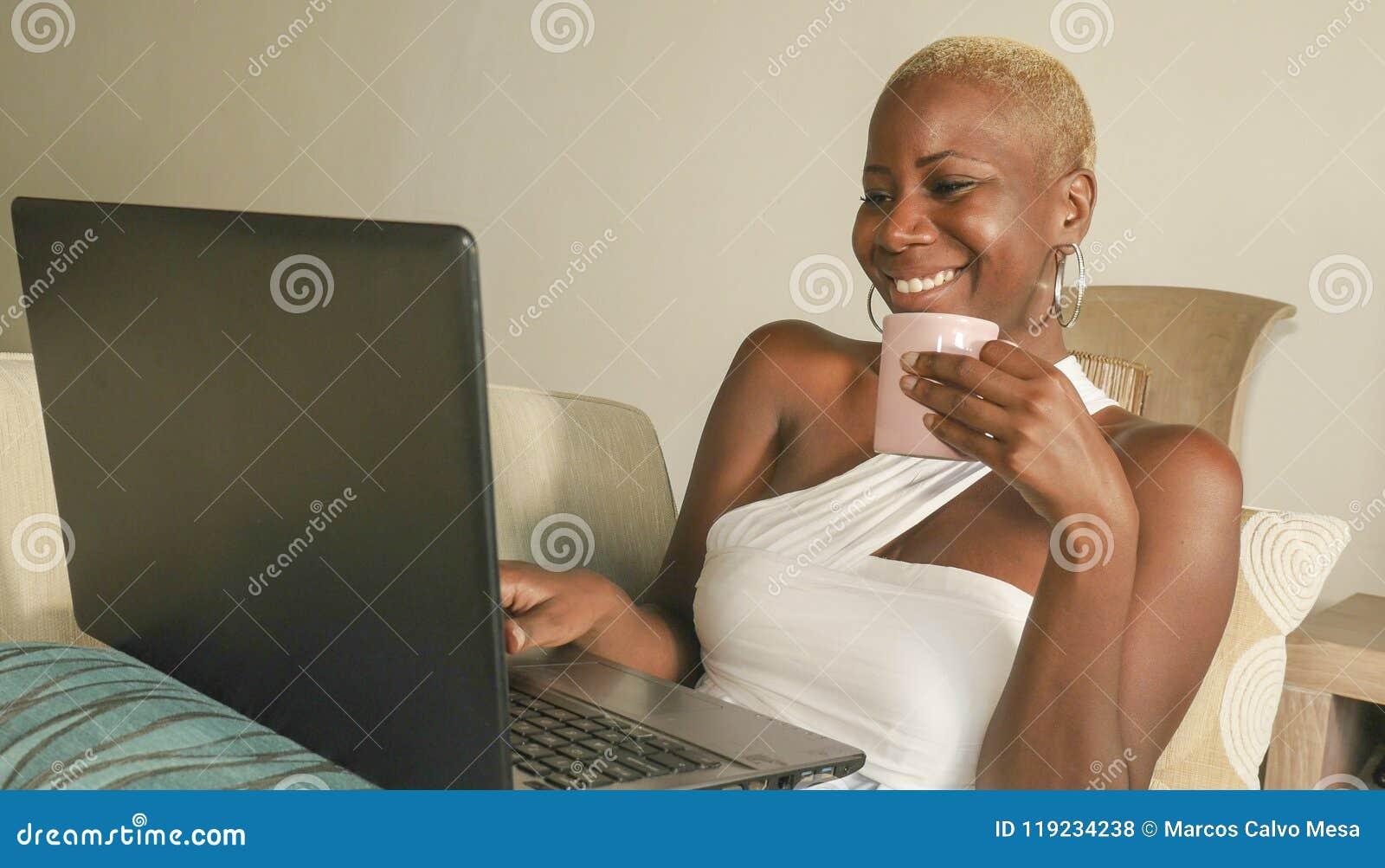 Het jonge mooie en gelukkige zwarte afro Amerikaanse vrouw opgewekt glimlachen hebbend pret op Internet die sociale media op lapt