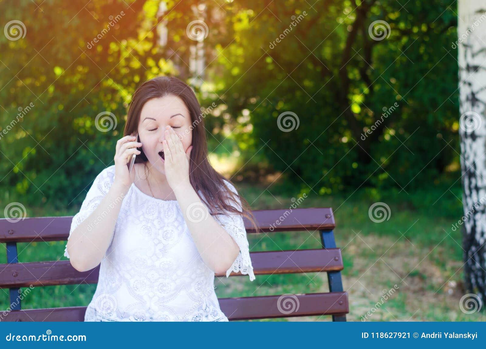 Het jonge mooie Europese meisjesbrunette spreekt op de telefoon in een stadspark en behandelt haar gezicht met haar handen Verras