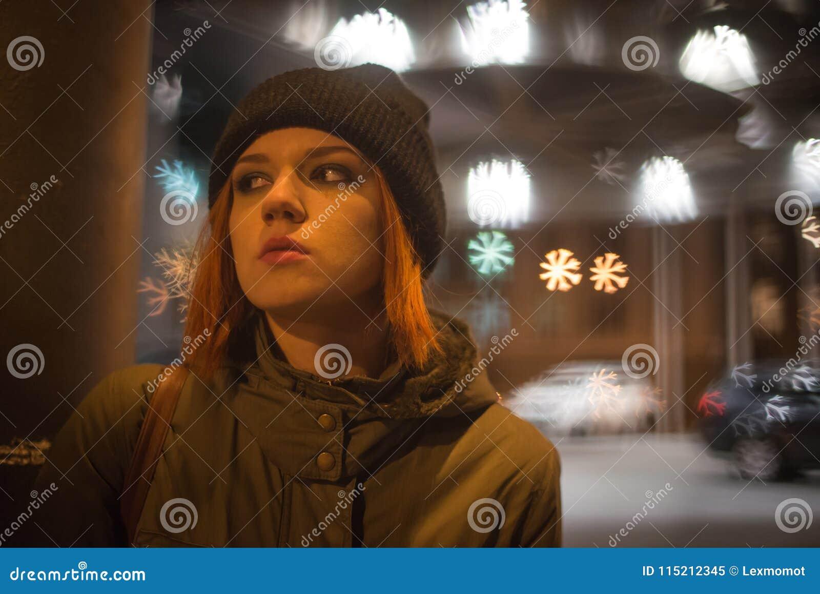 Het jonge mooie meisje haalt een taxi in de stadsstraat bij nacht
