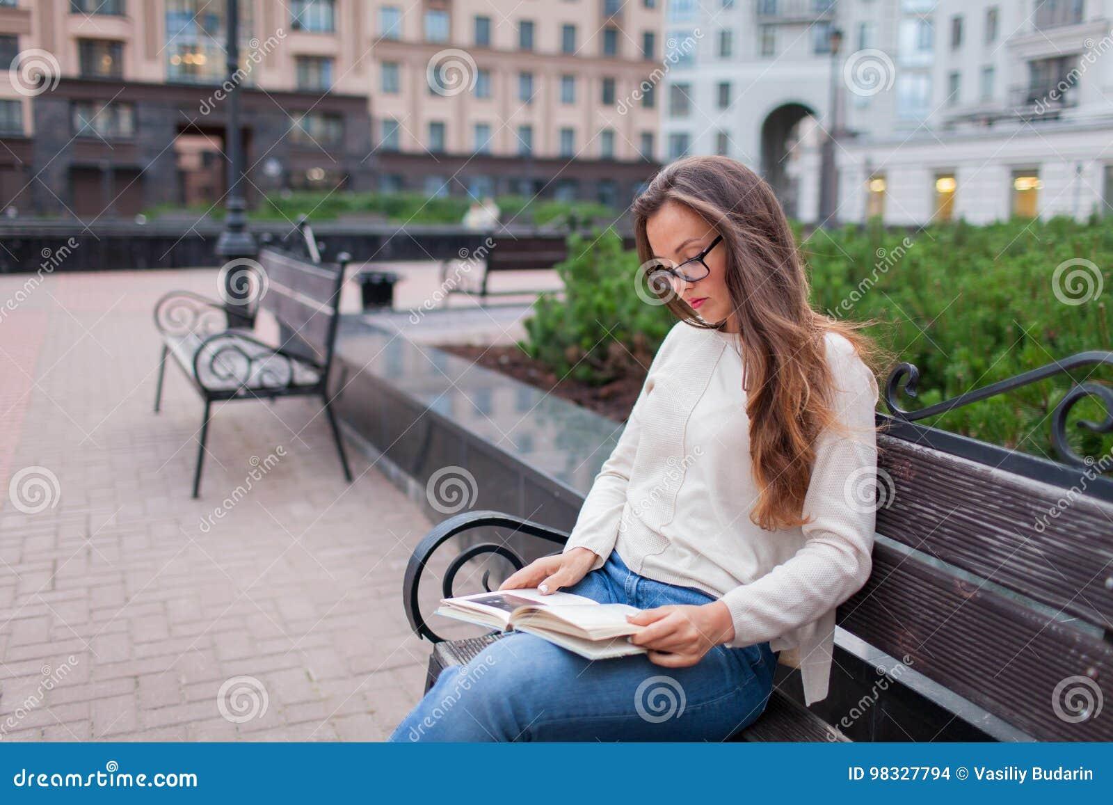 Het jonge mooie meisje met glazen snakt bruine haarzitting op een bank met een boek Zij verliet het huis op een warme avond aan b