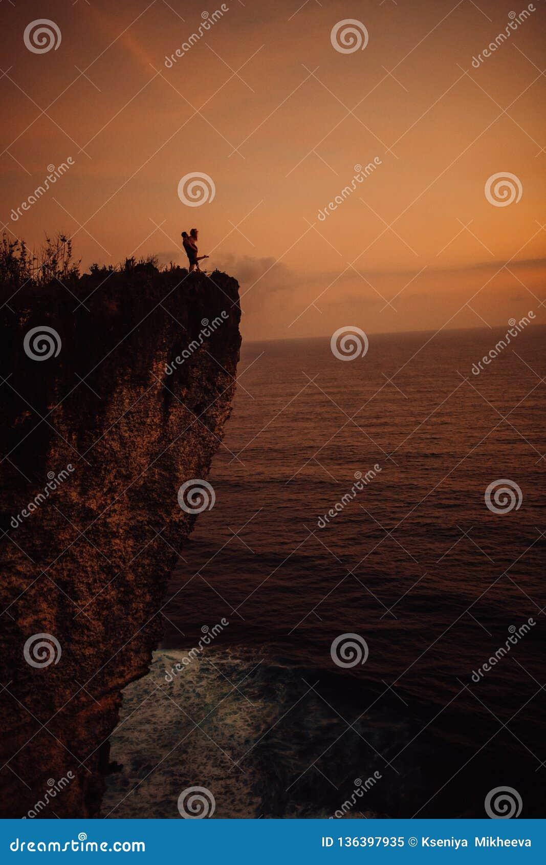 Het jonge mooie paar kussen bij zonsondergang dichtbij het overzees, silhouet
