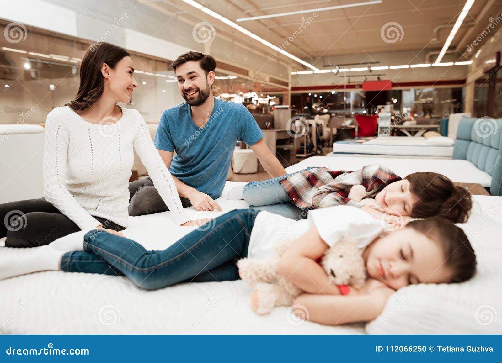 Het jonge mooie paar zit op matras naast slaapkinderen in meubilairopslag