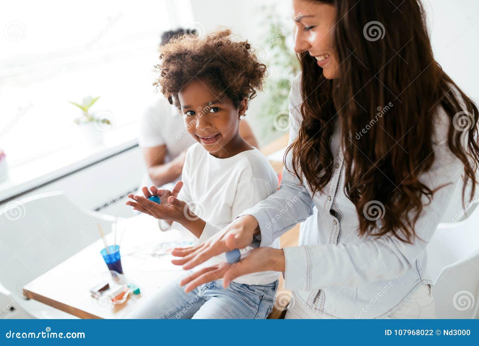 Het jonge mooie vrouw en jong geitje spelen met kleurrijke klei