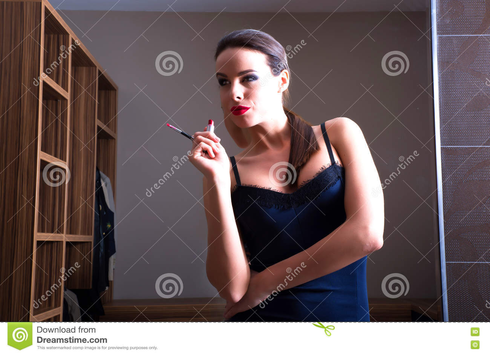 Het jonge mooie vrouw stellen voor een spiegel