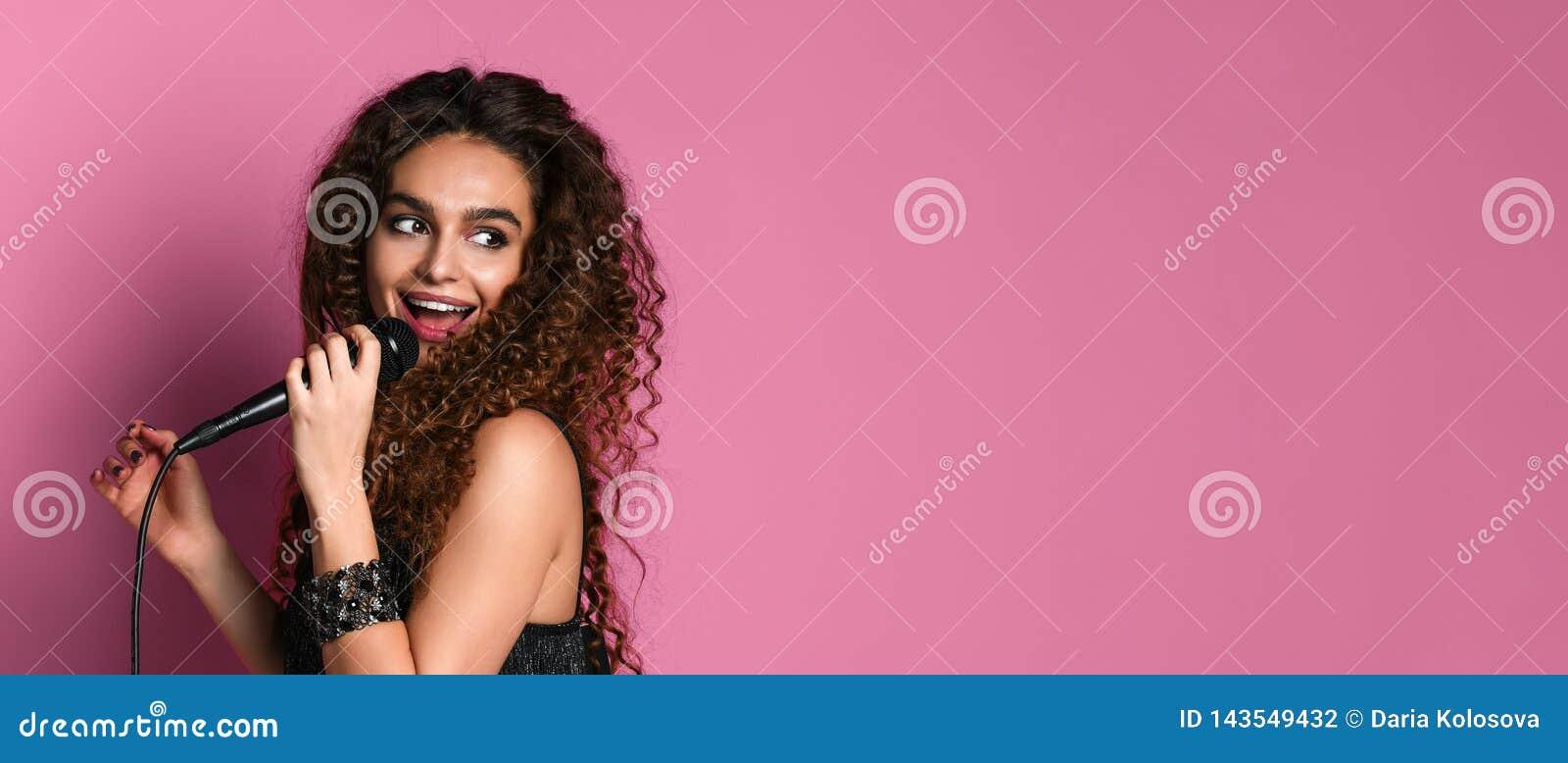 Het jonge mooie vrouw zingen in dicht omhoog geïsoleerde microfoon