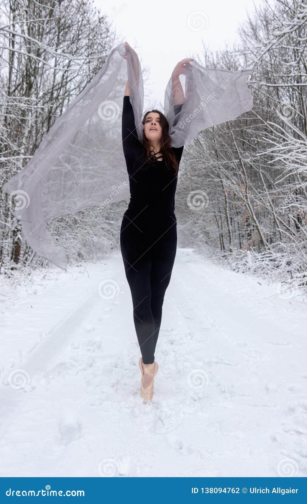 Het jonge mooie vrouwenmeisje in sneeuw de winterbos rekt zich uit en teen het dansen