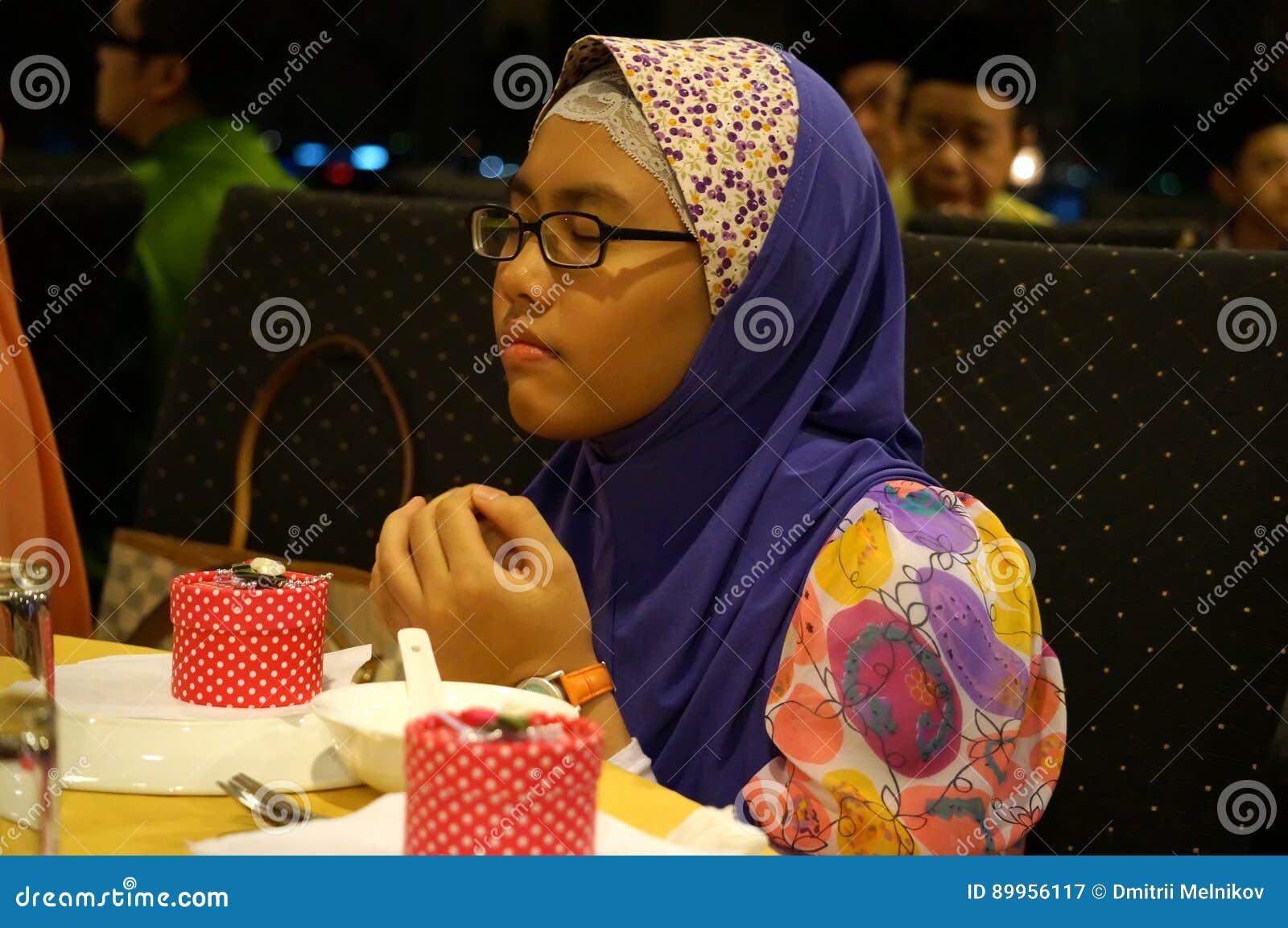Het jonge moslimmeisje bidden, Geïsoleerd op grijze achtergrond