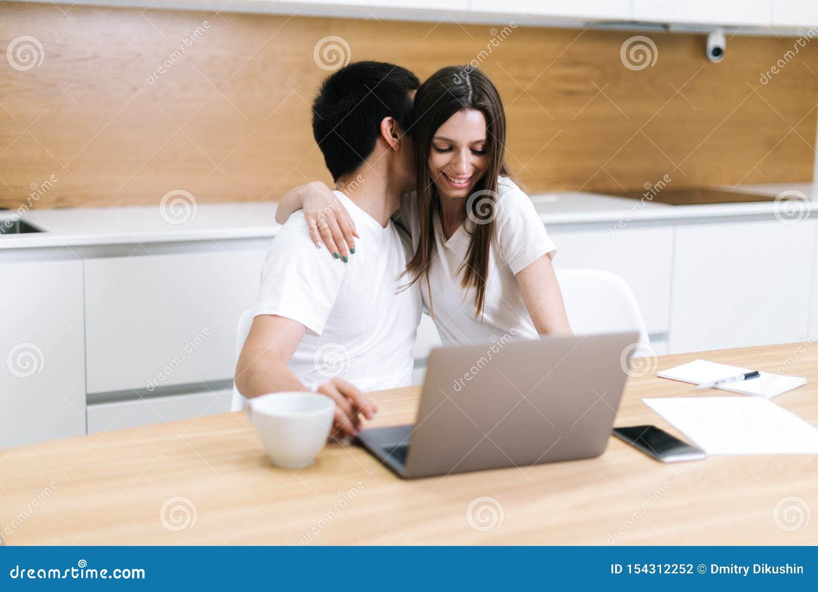 Het jonge het omhelzen paar gebruikt thuis laptop computerzitting op keuken