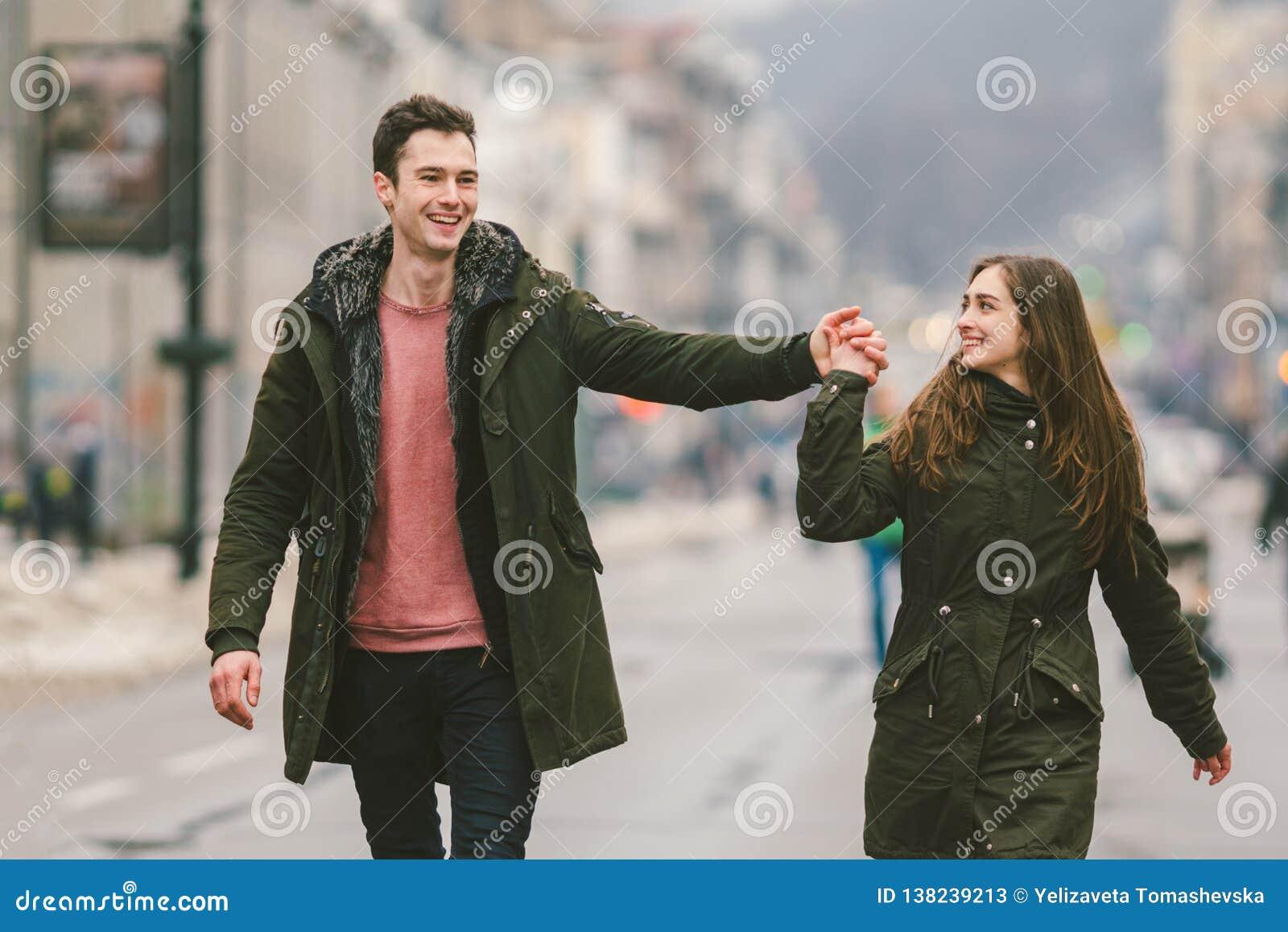 Het jonge paar, de heteroseksuele jongen en het meisje van Kaukasische nationaliteit, houdend van paar, lopen rond het centrum va