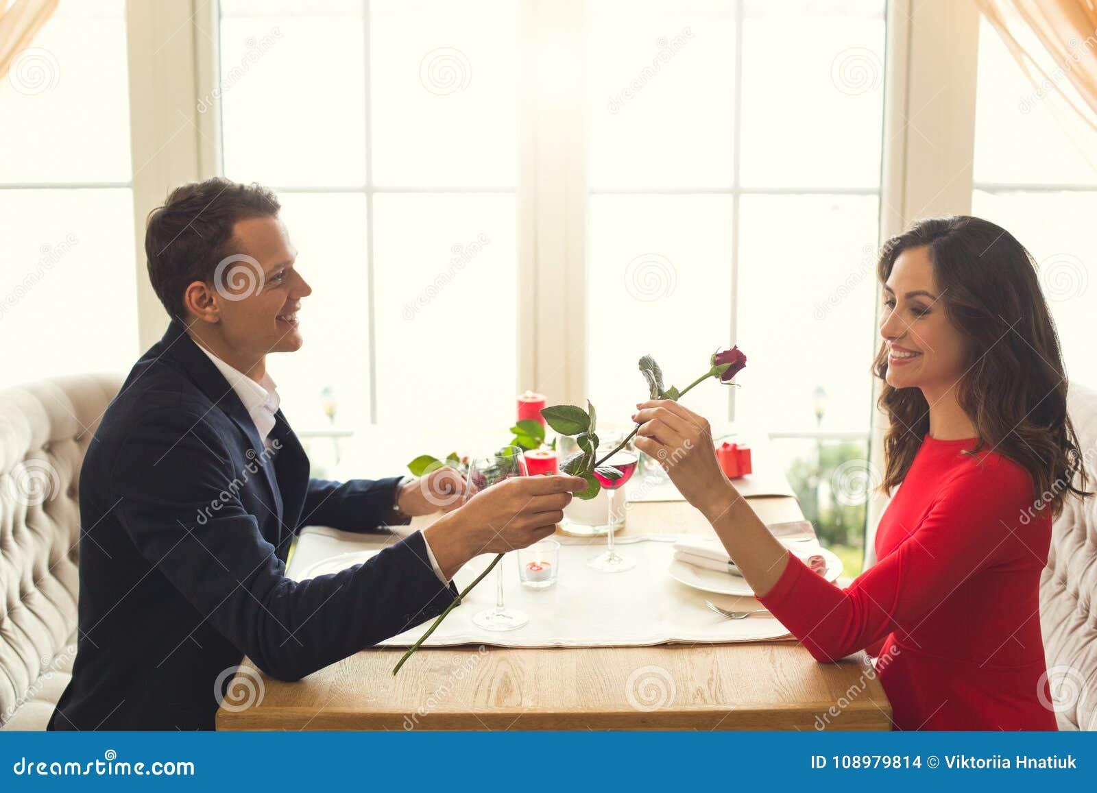 Het jonge paar die romantisch diner in het restaurant hebben nam bloemgift toe