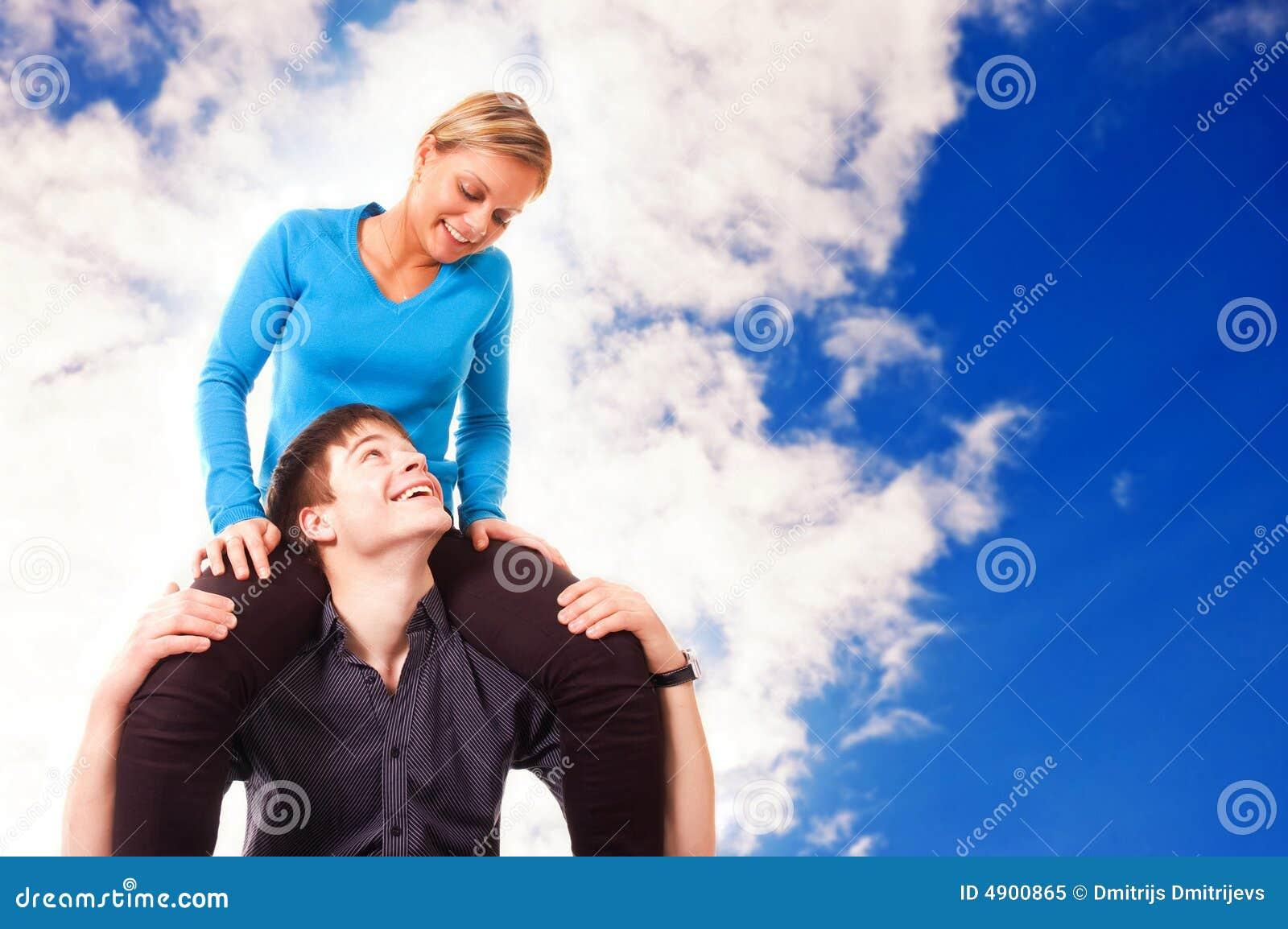 Het jonge paar heeft pret (blauwe hemelachtergrond)