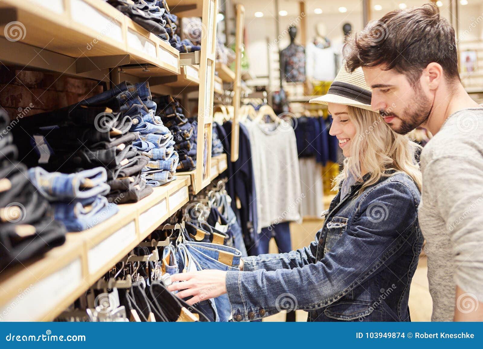 Het jonge paar in jeans vormt winkel terwijl het winkelen