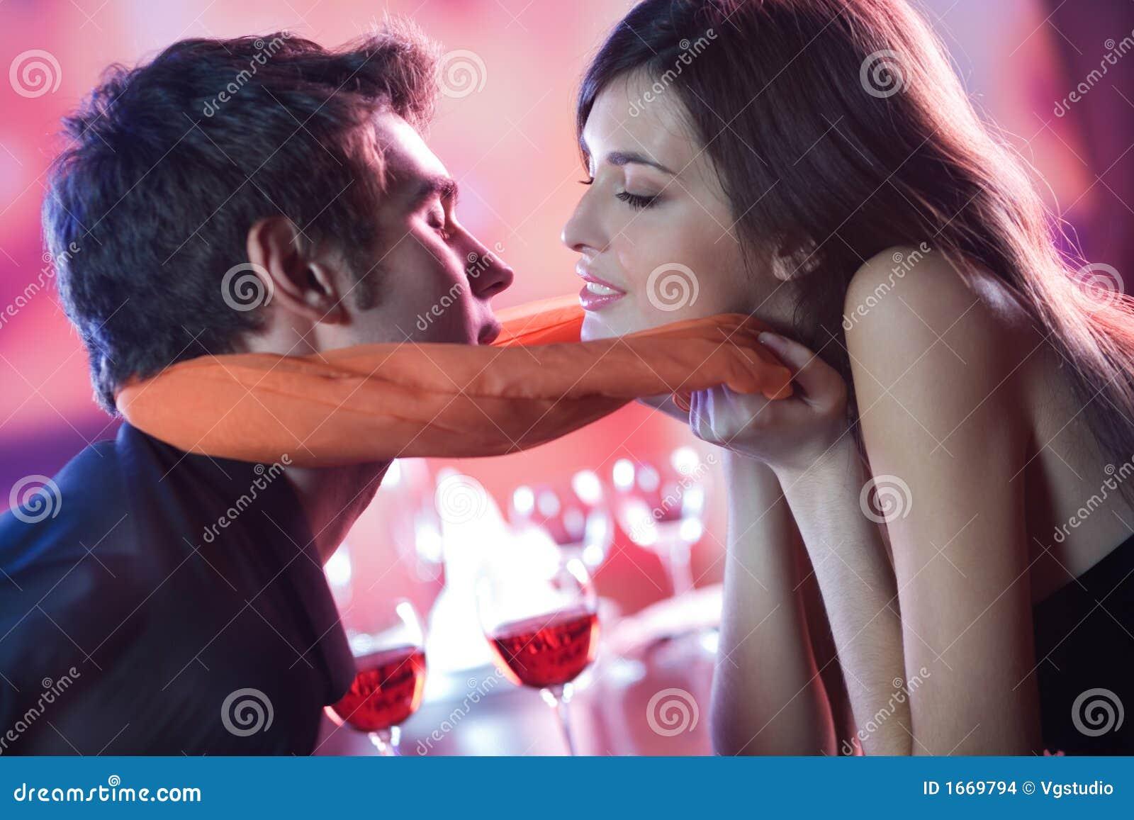 Het jonge paar kussen in restaurant, vierend of op romantische D