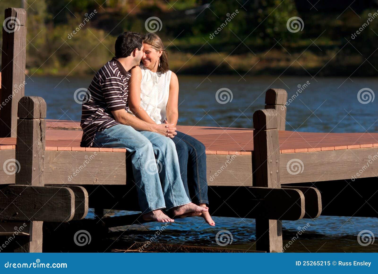 Het jonge Paar in Liefde zit blootvoets op Dok