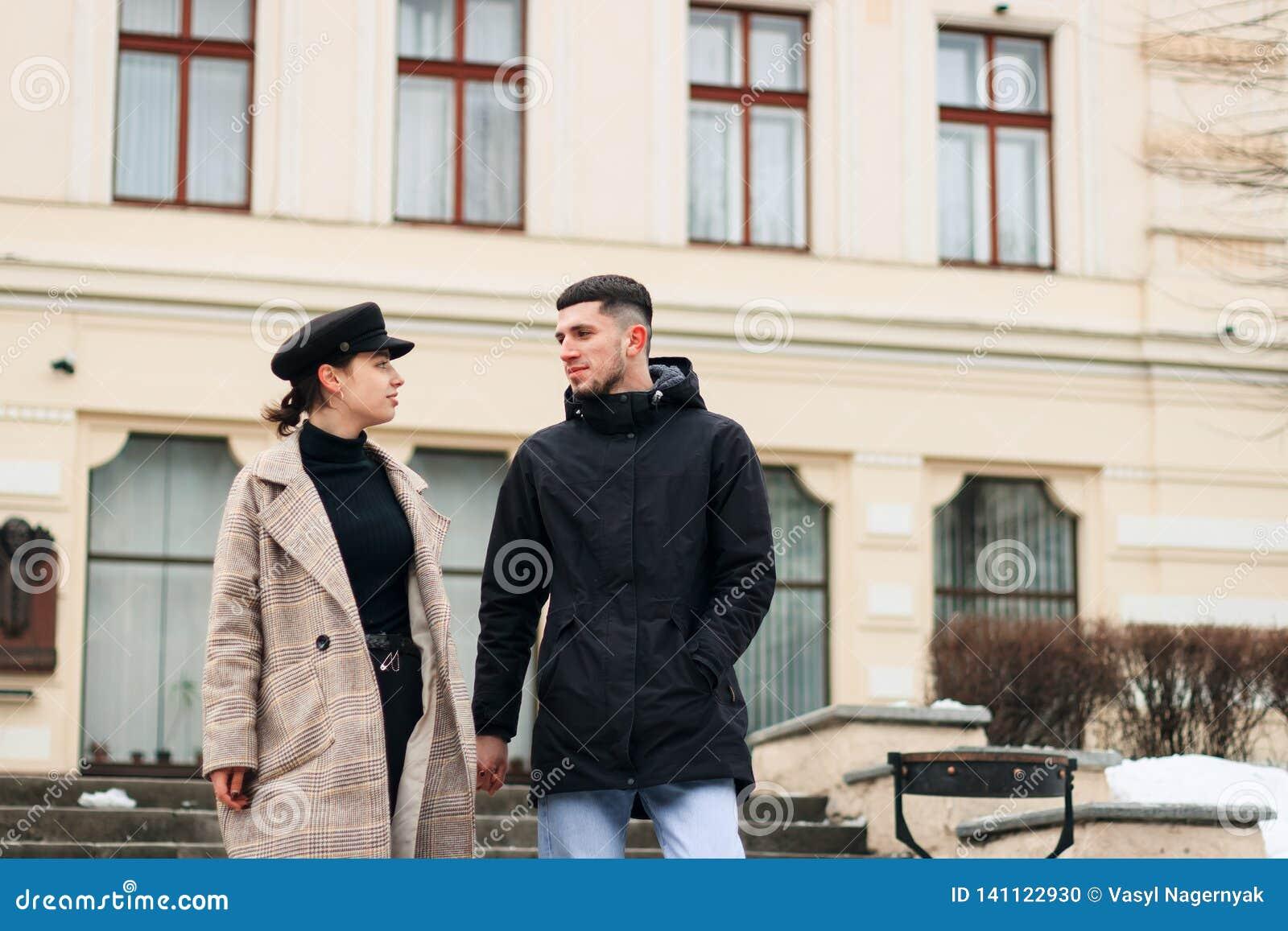 Het jonge paar van minnaars wandelt in de koele de winterochtend op de stadsstraten