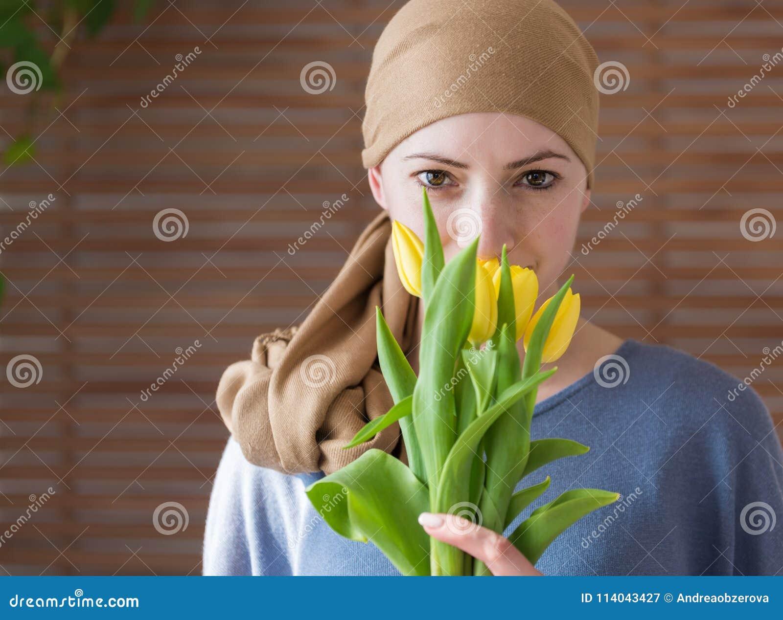 Het jonge positieve volwassen vrouwelijke boeket die van de kanker geduldige holding van gele tulpen, en camera glimlachen bekijk