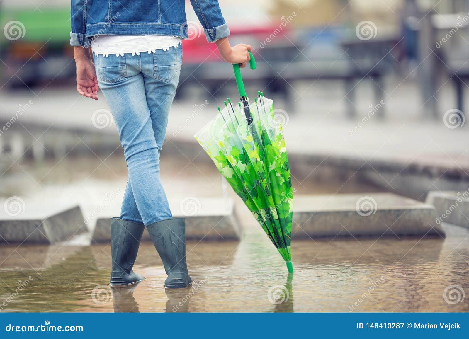 Het jonge pre-tienermeisje bevindt zich met een paraplu in vulklei na de lente of de zomerregen