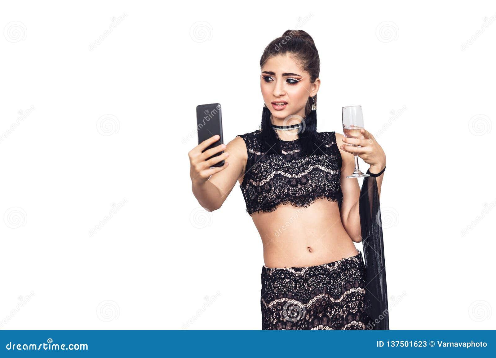Het jonge schitterende meisje houdt een glas van champagne en het nemen selfie